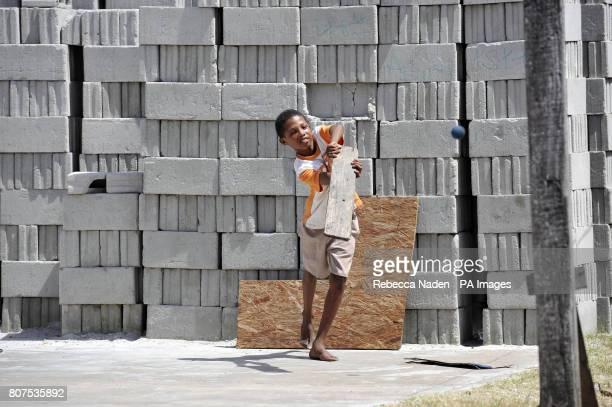 A young boy bats in a street cricket match in Georgetown Guyana