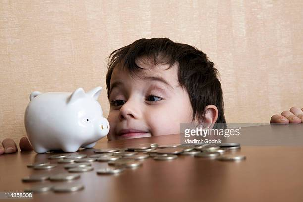 young boy behind table looking at piggybank