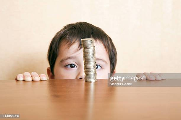 young boy behind table looking at pile of coins
