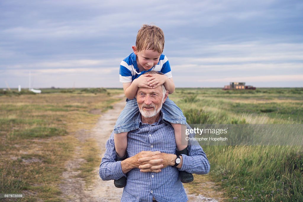 Young boy being carried by his grandad : Stock Photo