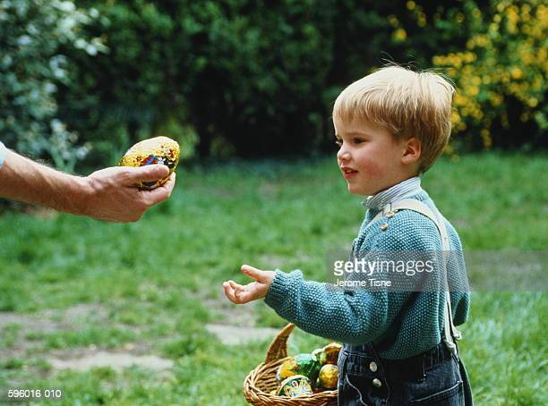 Young boy (4-5) being handed an Easter egg in garden