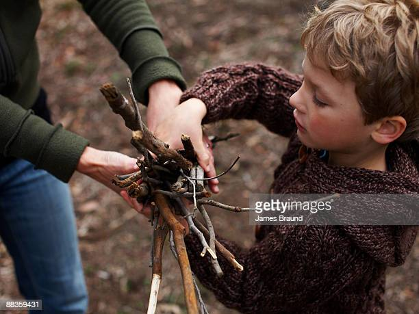 Young boy being handed sticks for campfire