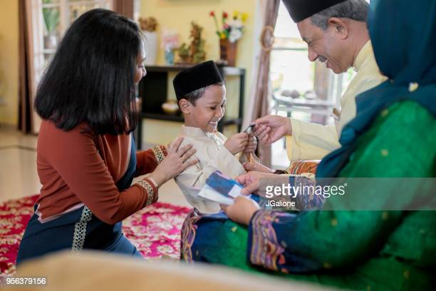 young boy being presented with a gift of money from his grandparents as part of the islamic celebration of hari raya aidilfitri (eid al-fitr) - eid mubarak stock pictures, royalty-free photos & images