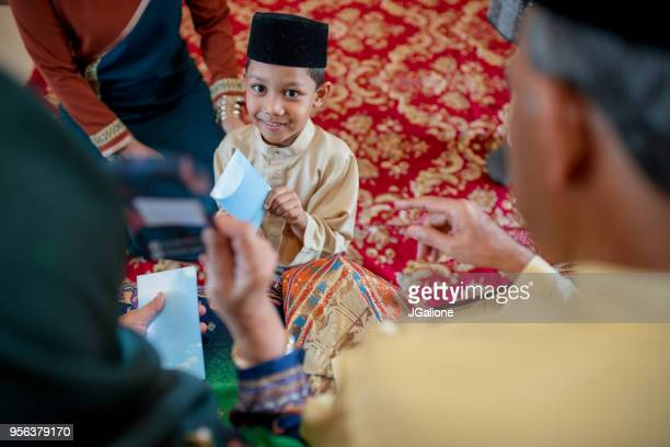 Young boy being presented with a gift of money from his grandparents as part of the Islamic celebration of Hari Raya Aidilfitri (Eid al-Fitr)