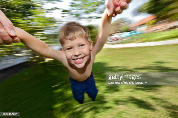 Young boy being spinning  around