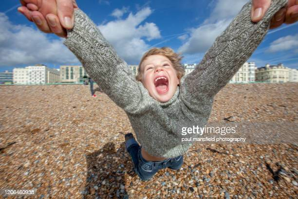 young boy being swung around on brighton beach - brighton beach england stock pictures, royalty-free photos & images