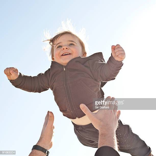 Young boy being tossed up in air, smiling