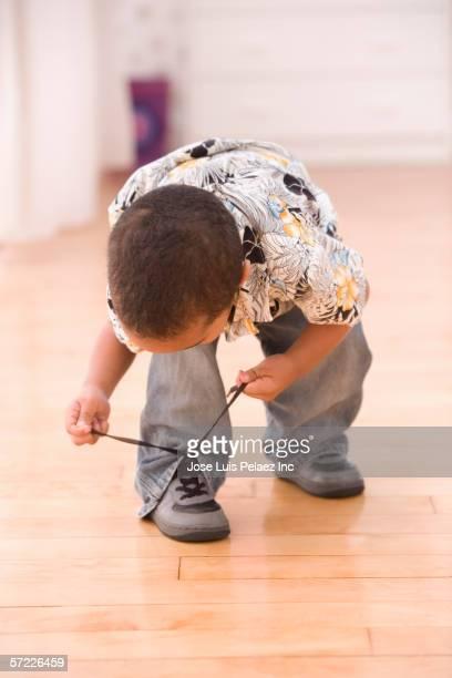 Young boy bent over tying shoe