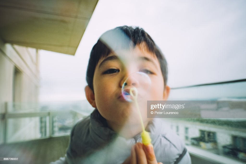 Young boy blowing bubbles : Stock Photo