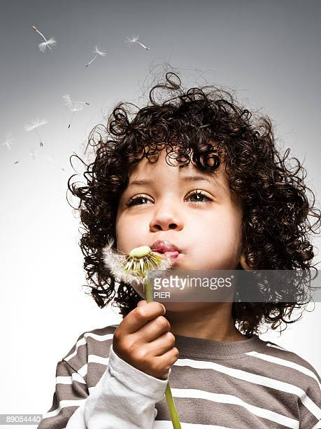 Young boy blowing dandelion seeds