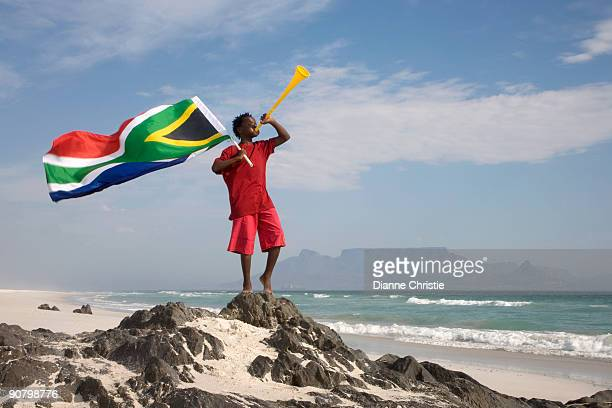 young boy blowing on vuvuzela, while holding south african flag on beach, table mountain in backgrou - south african flag stock photos and pictures
