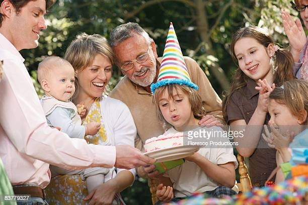 Young boy blowing out candles at party