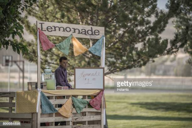 Young boy bored while waiting for customers at his lemonade stand.