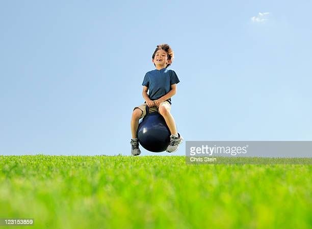 Young boy bouncing on a hill