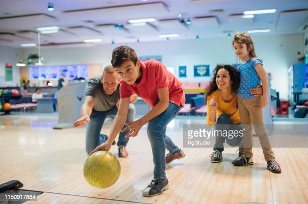 young boy bowling with family - bowling stock pictures, royalty-free photos & images