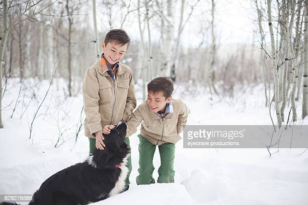 Young Boy Brothers and dog Outdoors in Winter Deep Snow