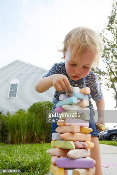 young boy building tower out of sidewalk chalk - foundation make up stock pictures, royalty-free photos & images