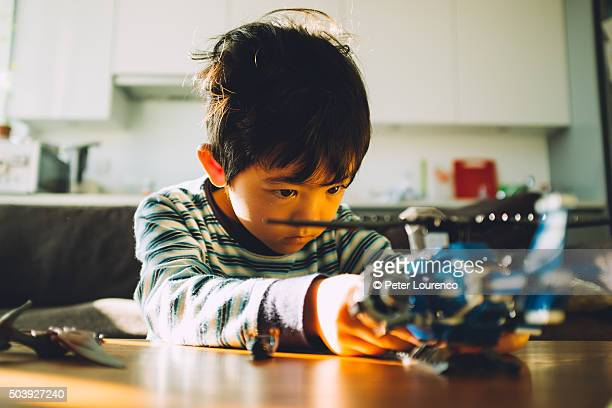 young boy building toy helicopter - peter lourenco stock pictures, royalty-free photos & images