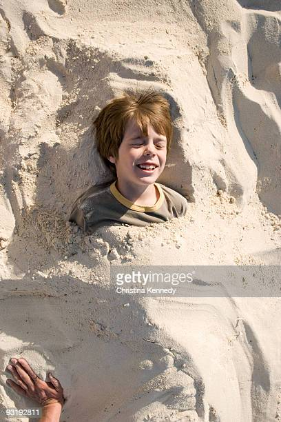 a young boy buried in sand, cable beach, nassau, bahamas, caribbean - cable beach bahamas stock photos and pictures
