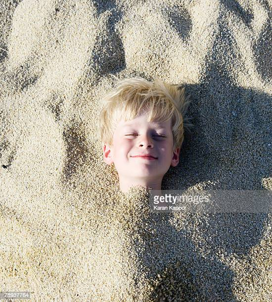 young boy buried in the sand smiling. - enterrar imagens e fotografias de stock