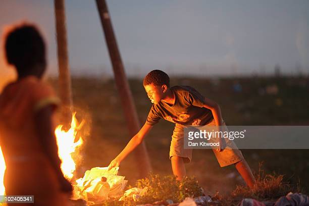 Young boy burns plastic and other waste in the New Brighton Township on June 24, 2010 in Port Elizabeth, South Africa. The New Brighton Township was...