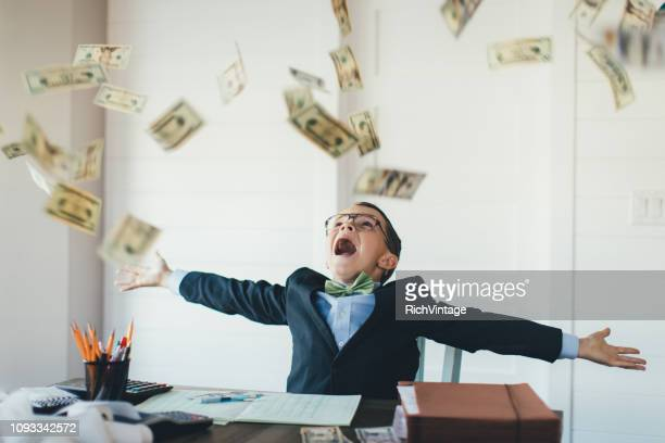 young boy businessman catching falling money - savings stock pictures, royalty-free photos & images