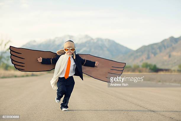 young boy businessman dressed in suit with cardboard wings - motivatie stockfoto's en -beelden
