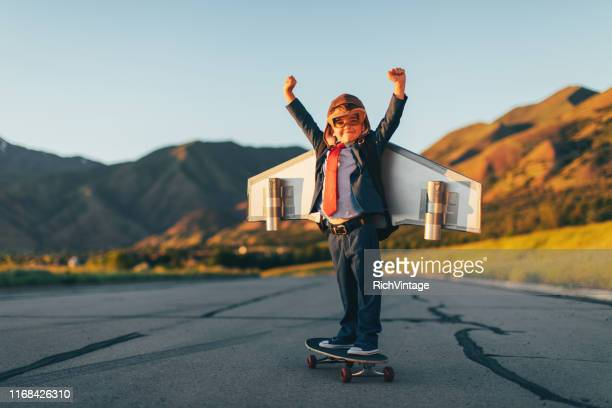 young boy businessman flying with jet pack on skateboard - return on investment stock pictures, royalty-free photos & images