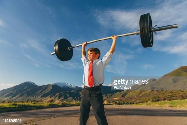 joven hombre de negocios levantando pesas - supervivencia fotografías e imágenes de stock