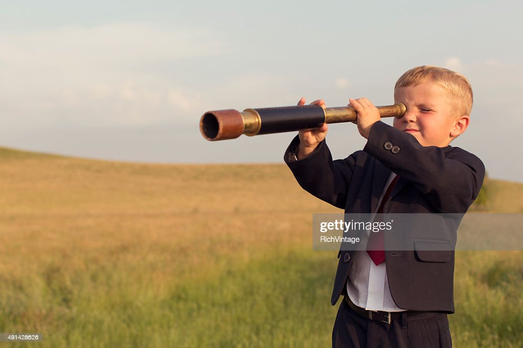 Young Boy Businessman Looking through Telescope : Stock Photo