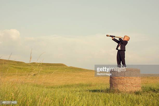 young boy businessman looking throught telescope - planning stockfoto's en -beelden