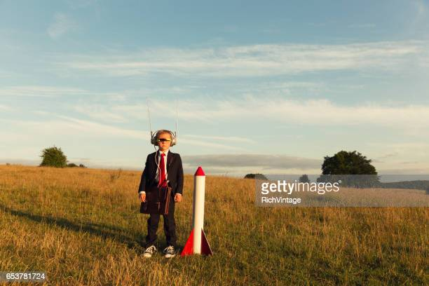 young boy businessman ready to launch rocket - festa per il lancio pubblicitario foto e immagini stock