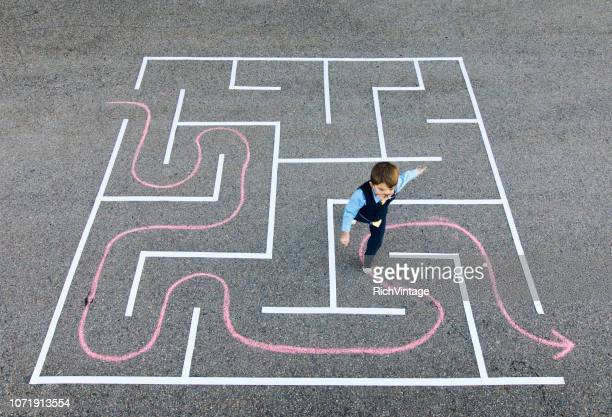 young boy businessman running in maze. - mistake stock pictures, royalty-free photos & images