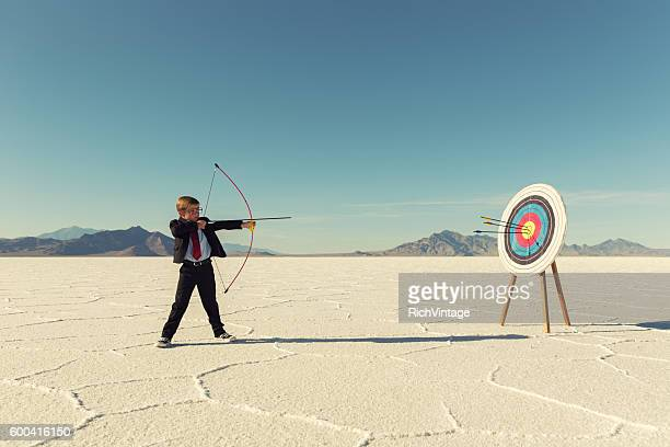 young boy businessman shoots arrows at target - vastberadenheid stockfoto's en -beelden