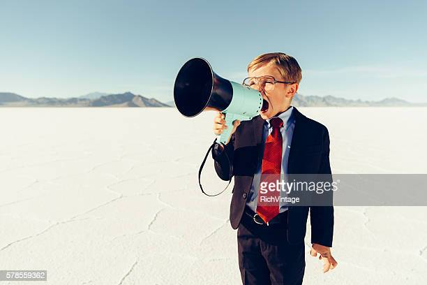 young boy businessman shouts through megaphone - day 7 fotografías e imágenes de stock