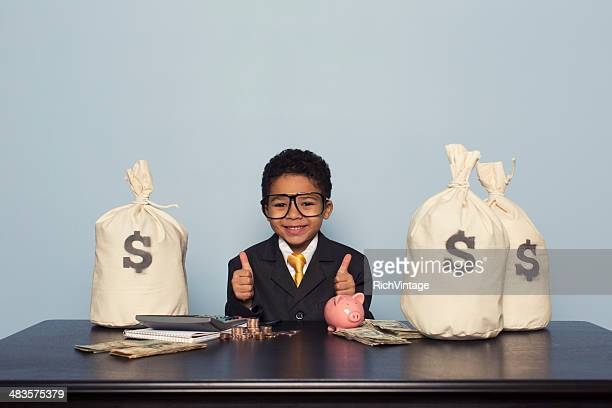 young boy businessman sits with u.s. money savings - vintage stock stock pictures, royalty-free photos & images