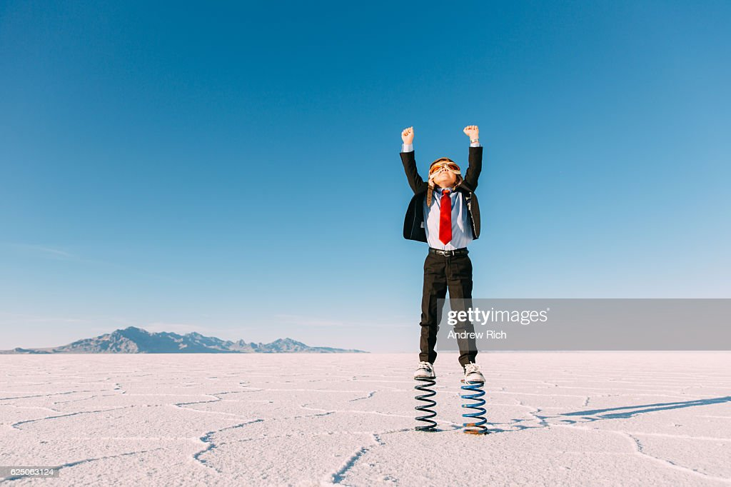 Young Boy Businessman Stands Arms Raised on Springs : Stockfoto