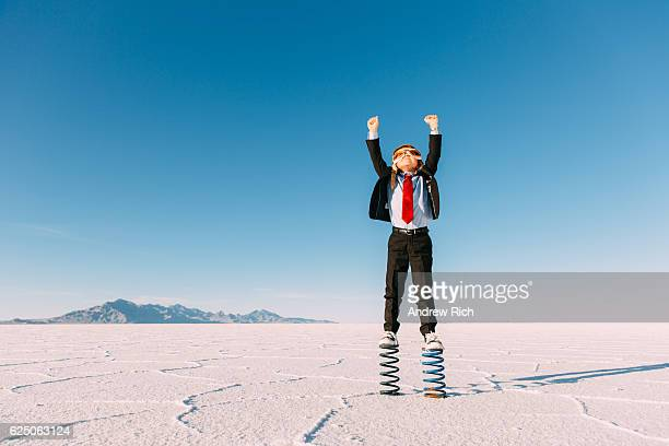 young boy businessman stands arms raised on springs - erwartung stock-fotos und bilder