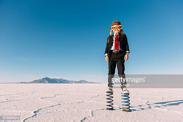 young boy businessman stands on giant springs - taking off activity stock pictures, royalty-free photos & images