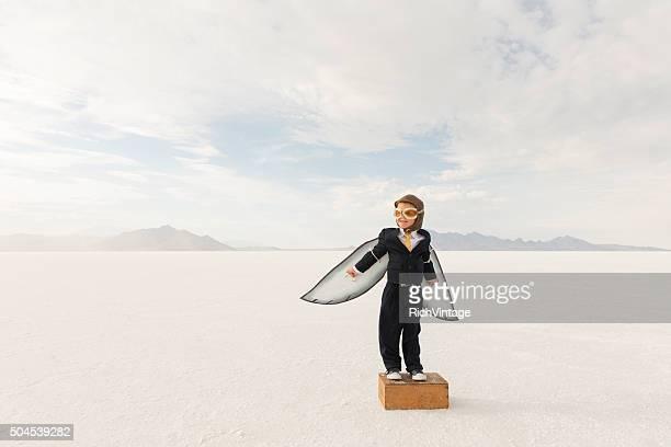 Young Boy empresario usando las alas de cartón