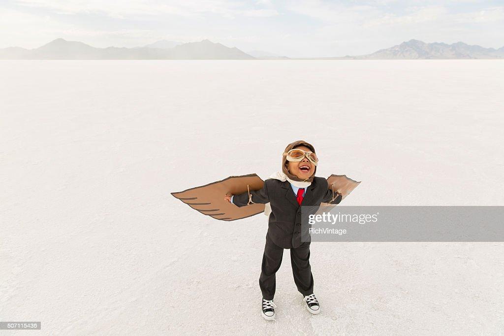 Young Boy Businessman Wearing Cardboard Wings : Stock Photo