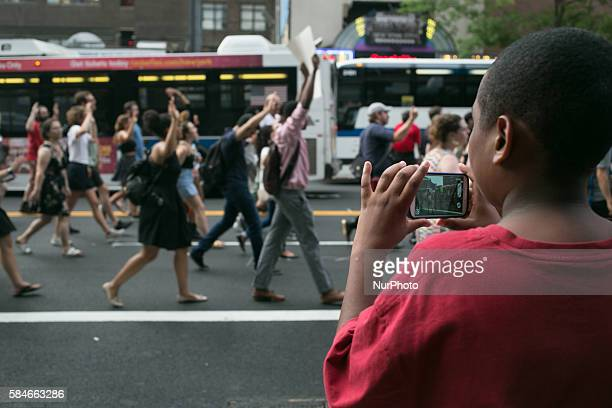A young boy captures the Black Lives Matter protest on his smartphone on July 7 2016 Activists were calling for an end to the epidemic of...