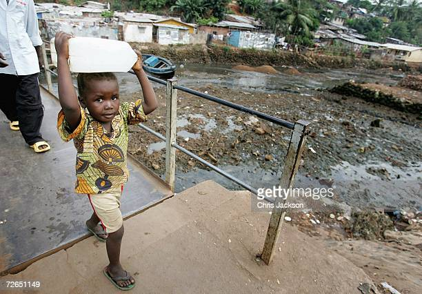 A young boy carries a container past a sewage strewn river on November 26 2006 in Freetown Sierra Leone Sierra Leone was ravaged by a decade long...