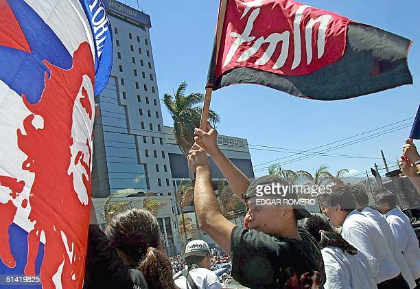 A young boy carries a Frente Farabundo Marti for the Liberacion Nacional flag and a portrait of Che Guevara during a protest against US president...