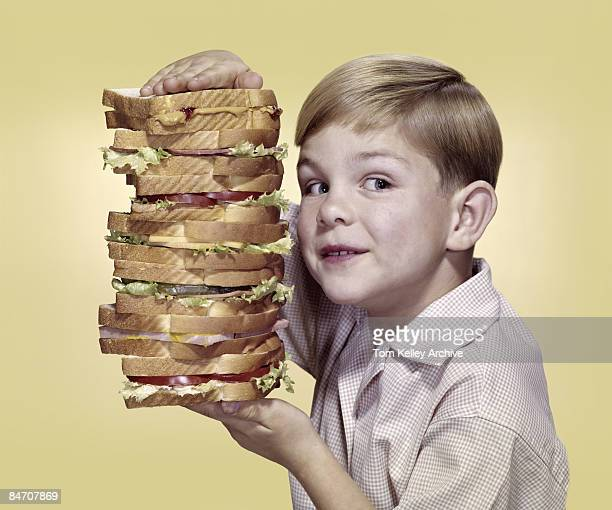 A young boy carries a huge multitiered 'Dagwood' sandwich United States