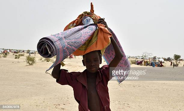 A young boy carries a mat in a camp for displaced populations near Diffa on June 16 2016 SANOGO