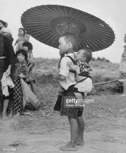 A young boy carries his baby brother on his back while shading themselves against the sun with an umbrella on a road somewhere in Okinawa 1945 The...