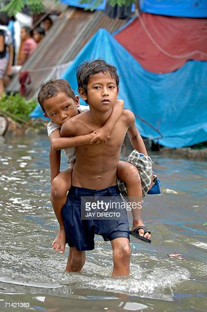 A young boy carries his brother as they walks through flood water in Malabon north of Manila 12 July 2006 Two children were missing and feared dead...