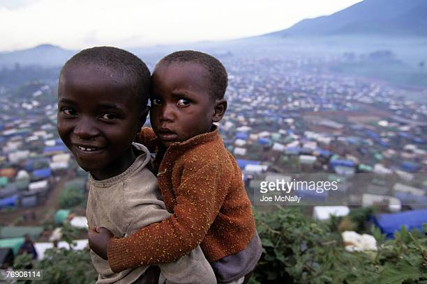 A young boy carries his sibling atop a hill overlooking the shanties in December of 1996 in Zaire Africa In 1994 Rwanda saw one of the worlds worst...