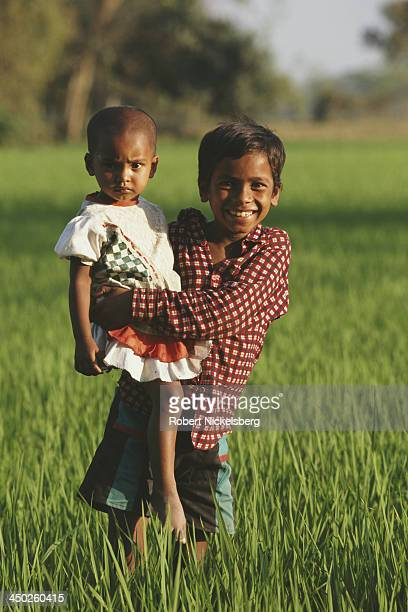 A young boy carries his sister through a rice field in Mymensingh Bangladesh circa 1991